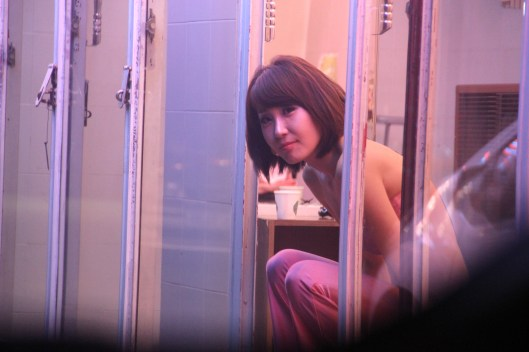 "A Korean prostitute in one of Korea's many ""pink light"" districts."