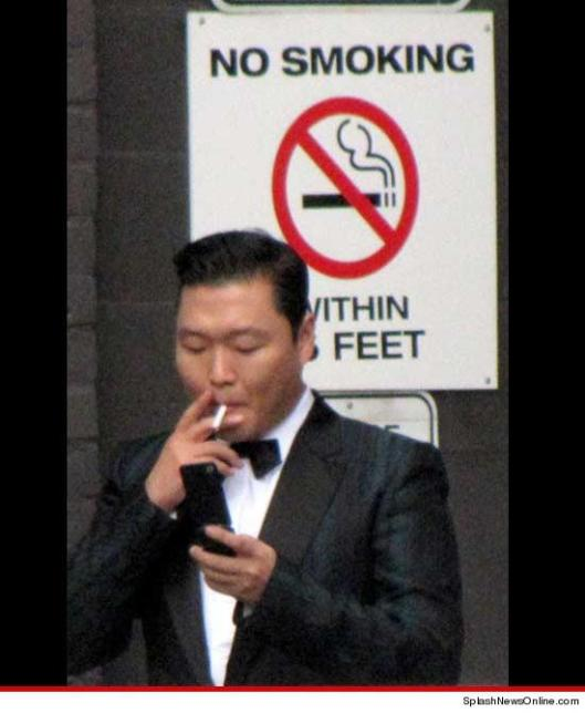 """PSY, who has no affiliation with the new Gangnam Cigarette brand, caught on camera smoking in front of a """"No Smoking"""" sigh."""